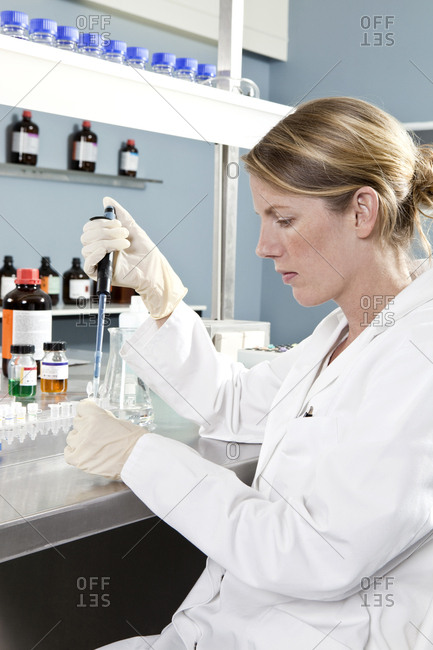A lab technician using a pipette to put a sample into a test tube