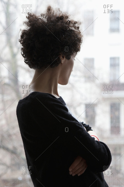 Side view of a woman looking through a window
