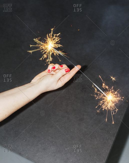 Cropped image of woman balancing sparklers on fingers