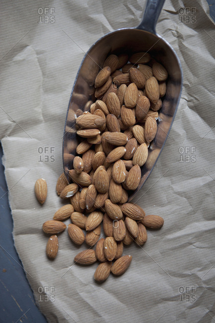 Almonds spilling from scoop on paper