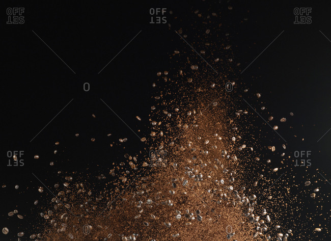 Ground coffee beans in mid-air against black background