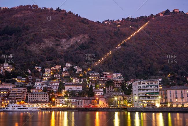 Lake Como area, Italy - November 21, 2017: Hillside city illuminated at dusk in the Lake Como area, Italy
