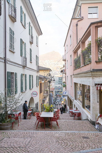 Lugano, Switzerland - November 22, 2017: Cobblestone street with outdoor dining tables