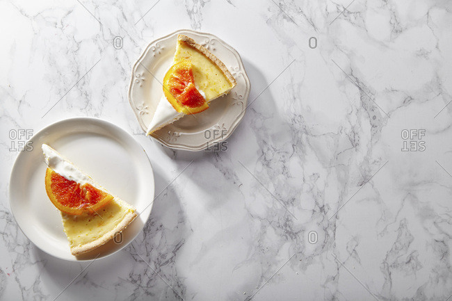 Slices of soft cheesecake with caramelized red oranges and whipped cream