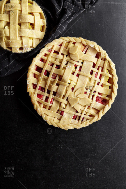 Pie crust design ideas - various ways of pie decoration with lattice and leaves Apple, strawberry and raspberry pies uncooked on black table