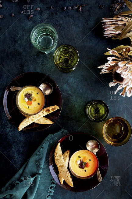 Wine Roasted Vegetable Bisque served with bread and wine Photographed on a dark blue background