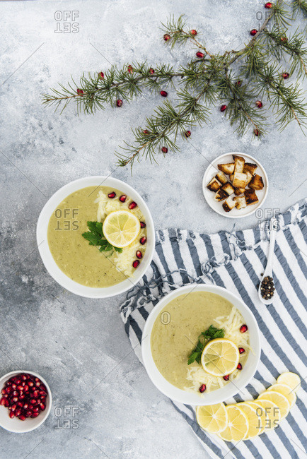 Cheesy broccoli soup in two bowls topped with pomegranate arils, herbs and lemon slices