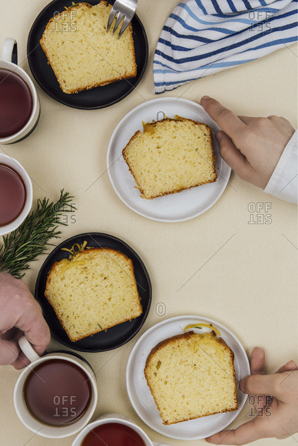 People grabbing kefir lemon bread slices served on plates and tea from a breakfast table