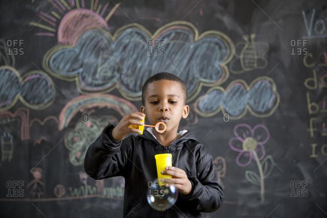 School boy blowing bubbles in class