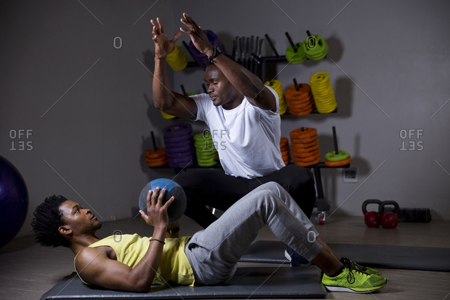 African man working with trainer in gym