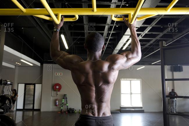 African man training on bar in gym