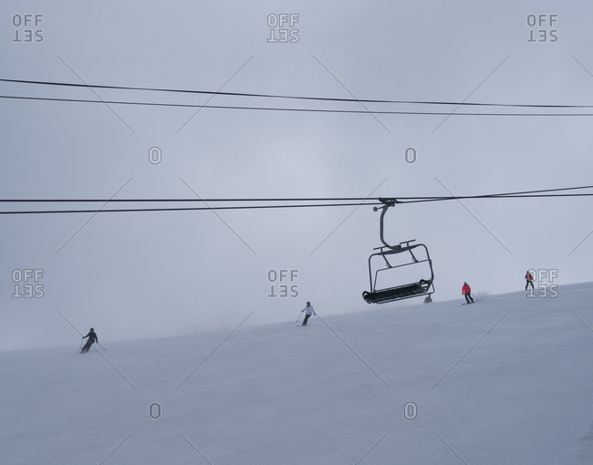 Skiers making their way down the slope in poor visibility with chair lift in the foreground