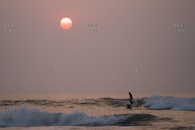 Surfer on a wave under sky turned pink by wildfires