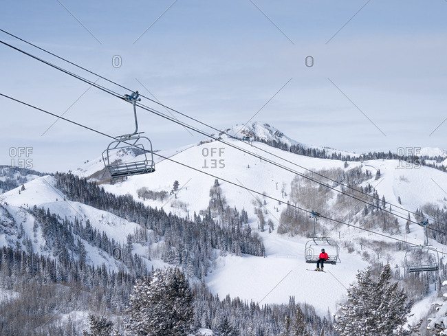 Lone skier on chair lift with snowy landscape as backdrop