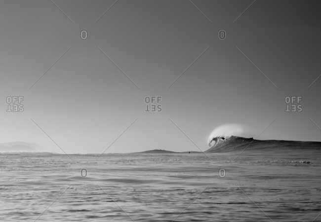 Surfer dropping into large breaking wave