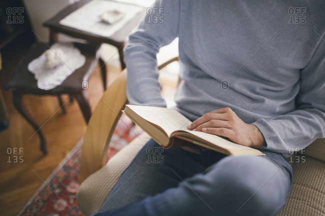 Man reading book at home