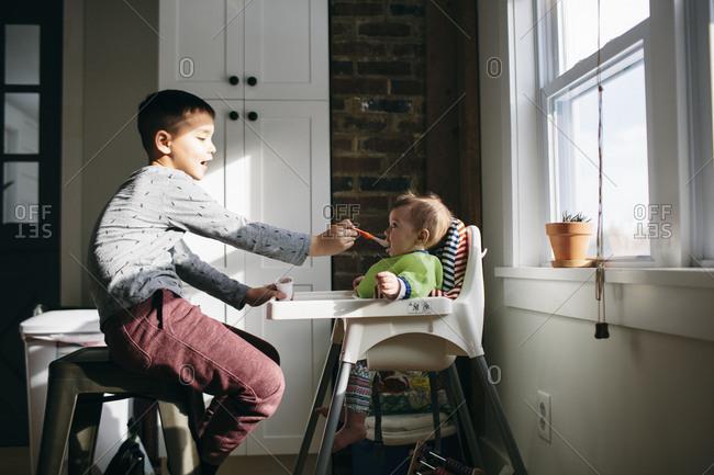 Boy feeding baby in a highchair