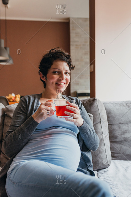 Portrait of 9 month pregnant woman drinking tea