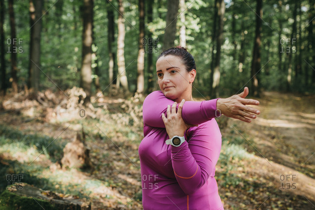 Portrait of a female jogger getting ready for a jog and doing some stretches in a forest