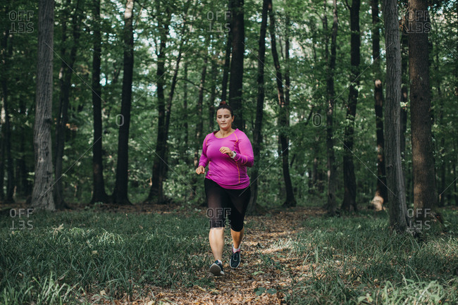 Front view of a focused female runner and jogging in a forest