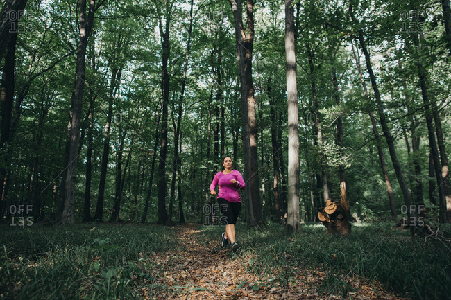 Front view of a focused female runner jogging in a forest