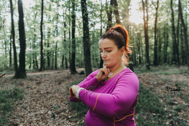 Portrait of a plus size female jogger measuring her pulse after a jog in a park