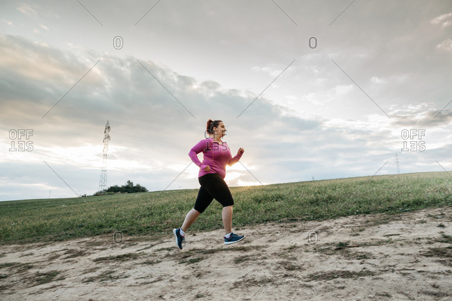 Low angle view of a plump female jogger jogging up a hill at sunset