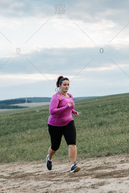 A full length portrait of a determined female runner running up a hill and trying to stay fit
