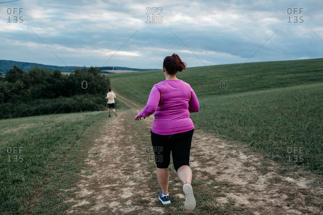 Back view of a woman in sportswear running after a man along a country trail