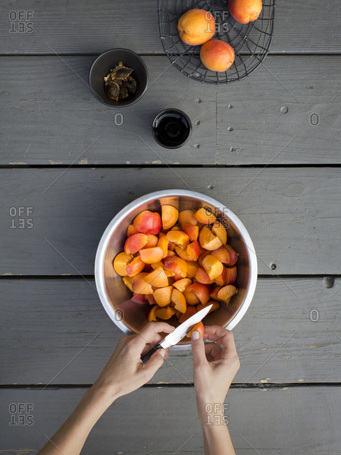 A person cutting apricots into a bowl