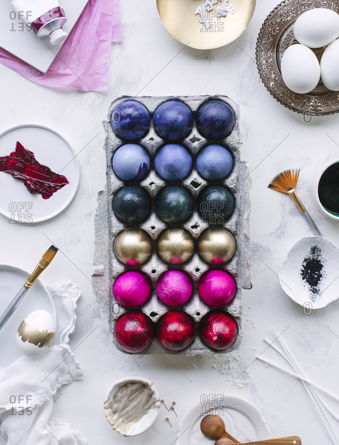 Painting supplies surrounding multicolored Easter eggs