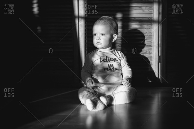 Baby sitting on floor in black and white