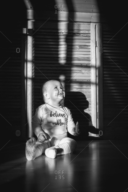 Happy baby sitting on floor in black and white