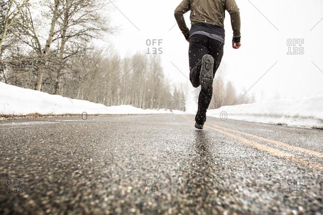 Man running on road during winter