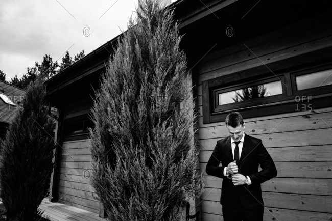 Young stylish groom outdoors in a tuxedo