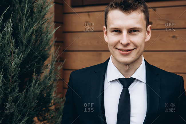 Close-up portrait of an attractive smiling groom in a tuxedo