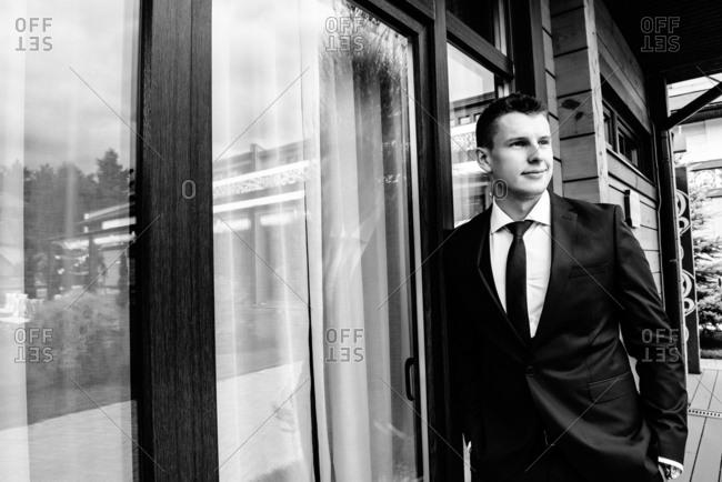 Groom in a black tuxedo standing outdoors near a large window