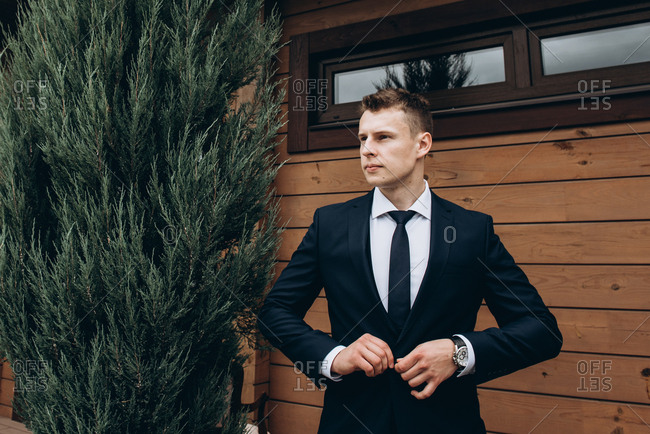Bridegroom in a black tuxedo stands outdoors on his wedding day
