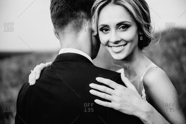 Smiling bride hugs her beloved groom