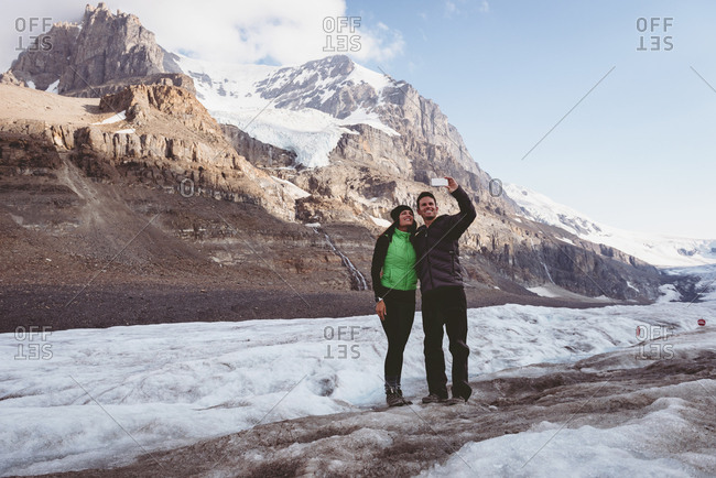 Couple taking selfie with mobile phone near mountain