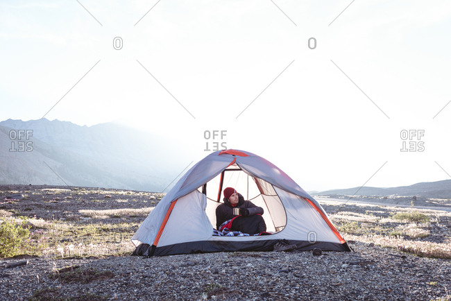 Man having coffee in tent on a sunny day