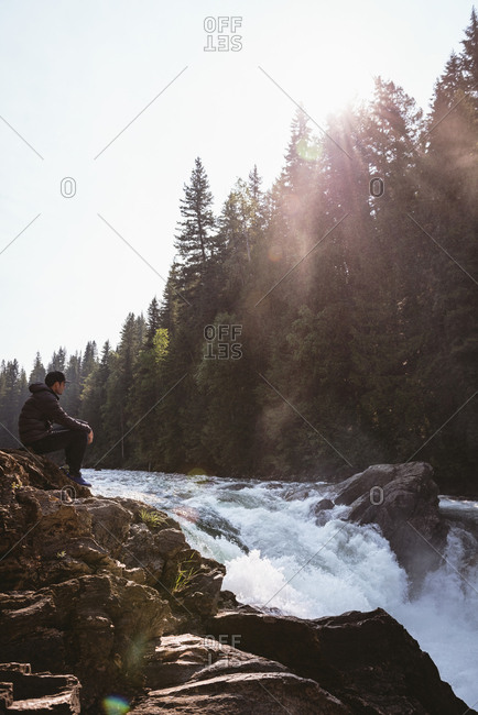 Man sitting on rock near waterfall on a sunny day