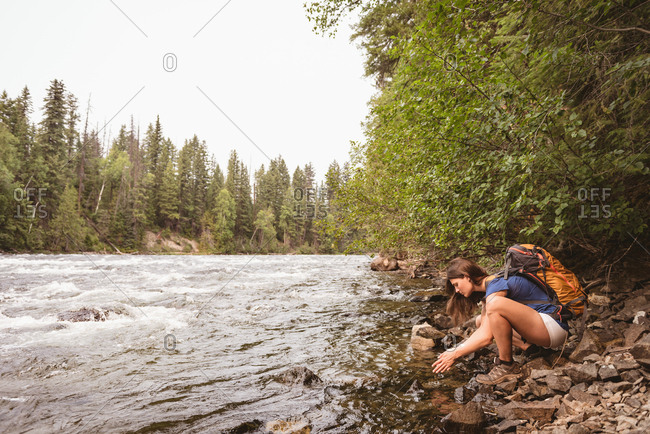 Side view of woman washing her hand in river