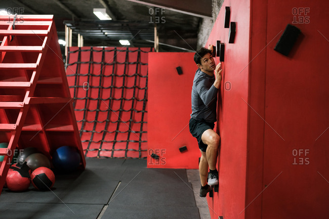Man practicing rock-climbing on a wall in fitness studio