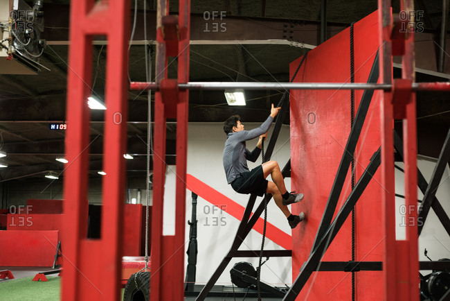 Muscular man climbing a wall with rope in the gym