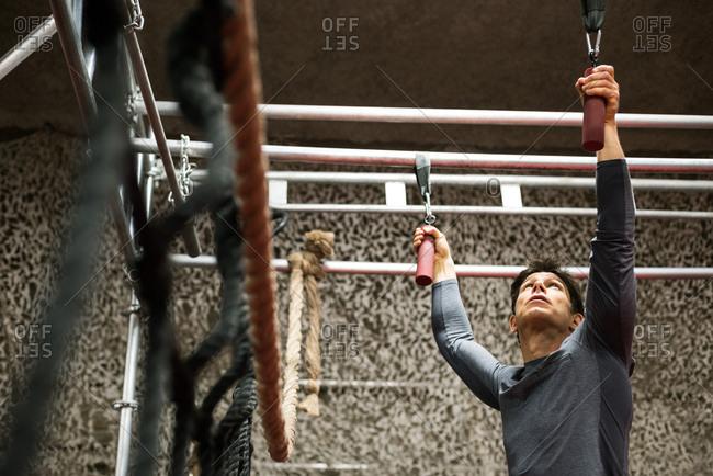 Muscular man exercising on monkey bar in fitness studio