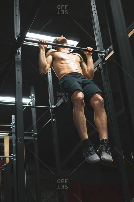 Muscular man practicing pull up on a pull up bar at the gym