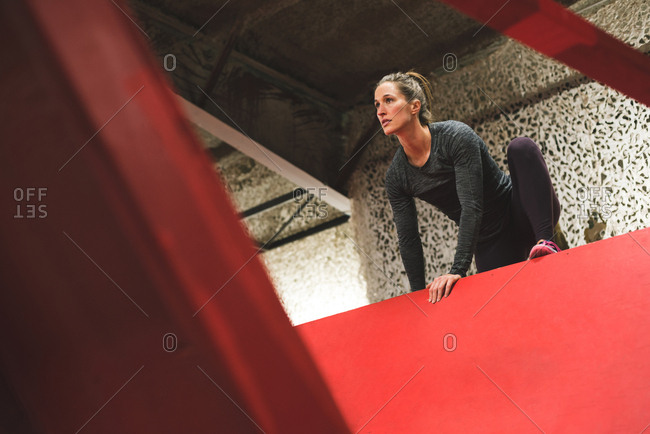Muscular woman climbing a wall in the gym
