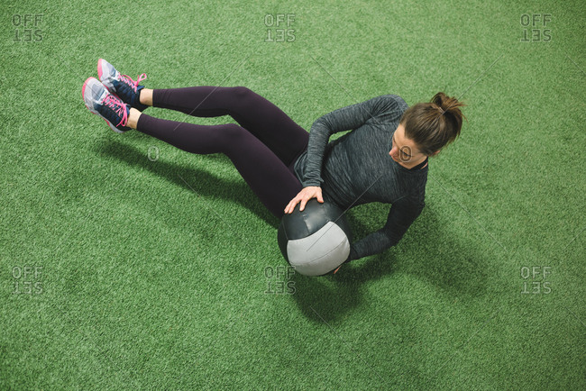 Woman practicing stretching with a ball on turf