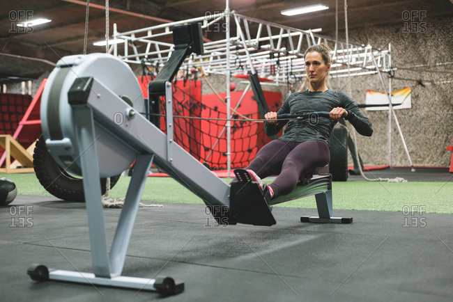 Muscular woman exercising on rowing machine at gym